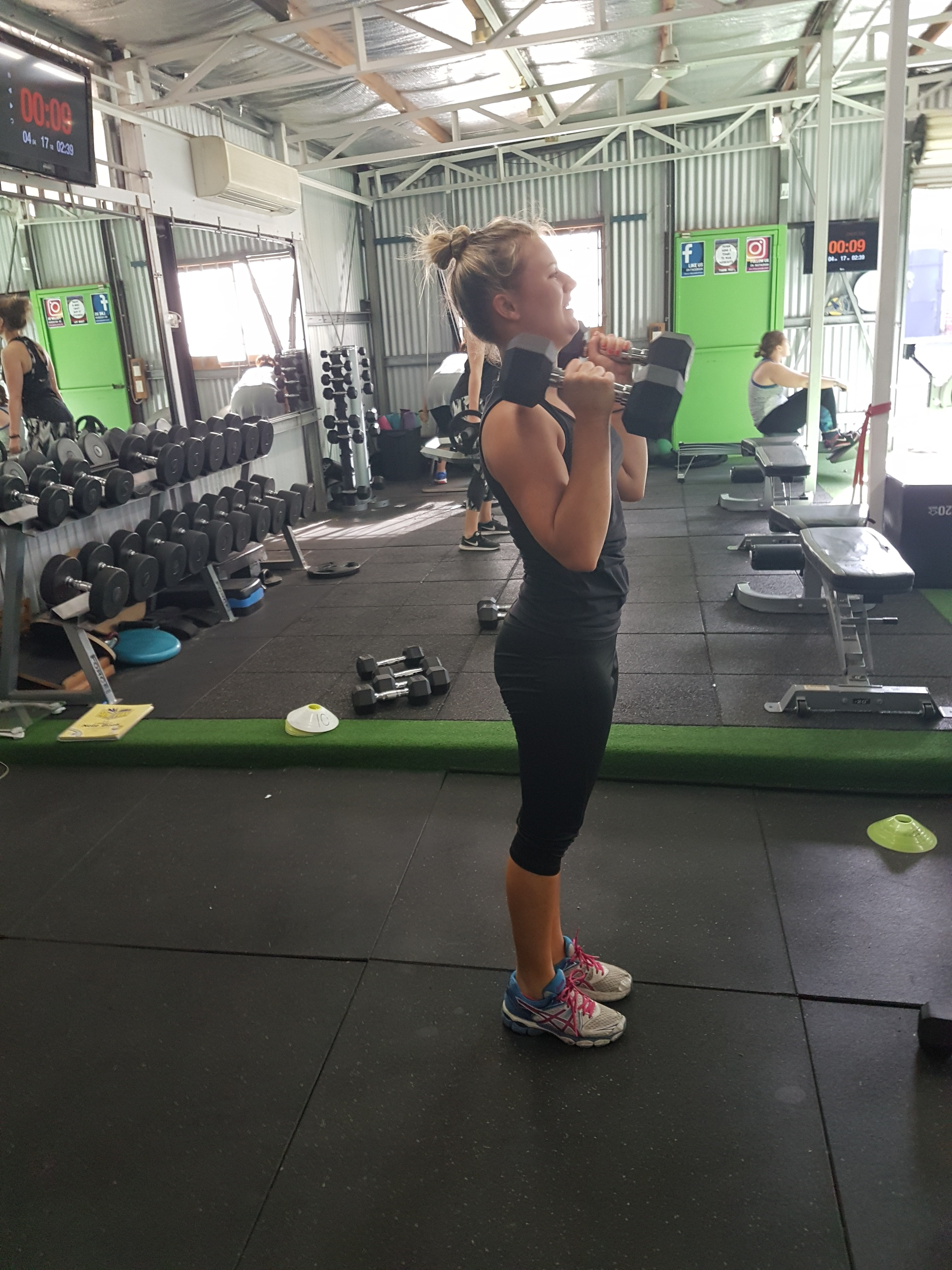 bicep curls with client in our gym