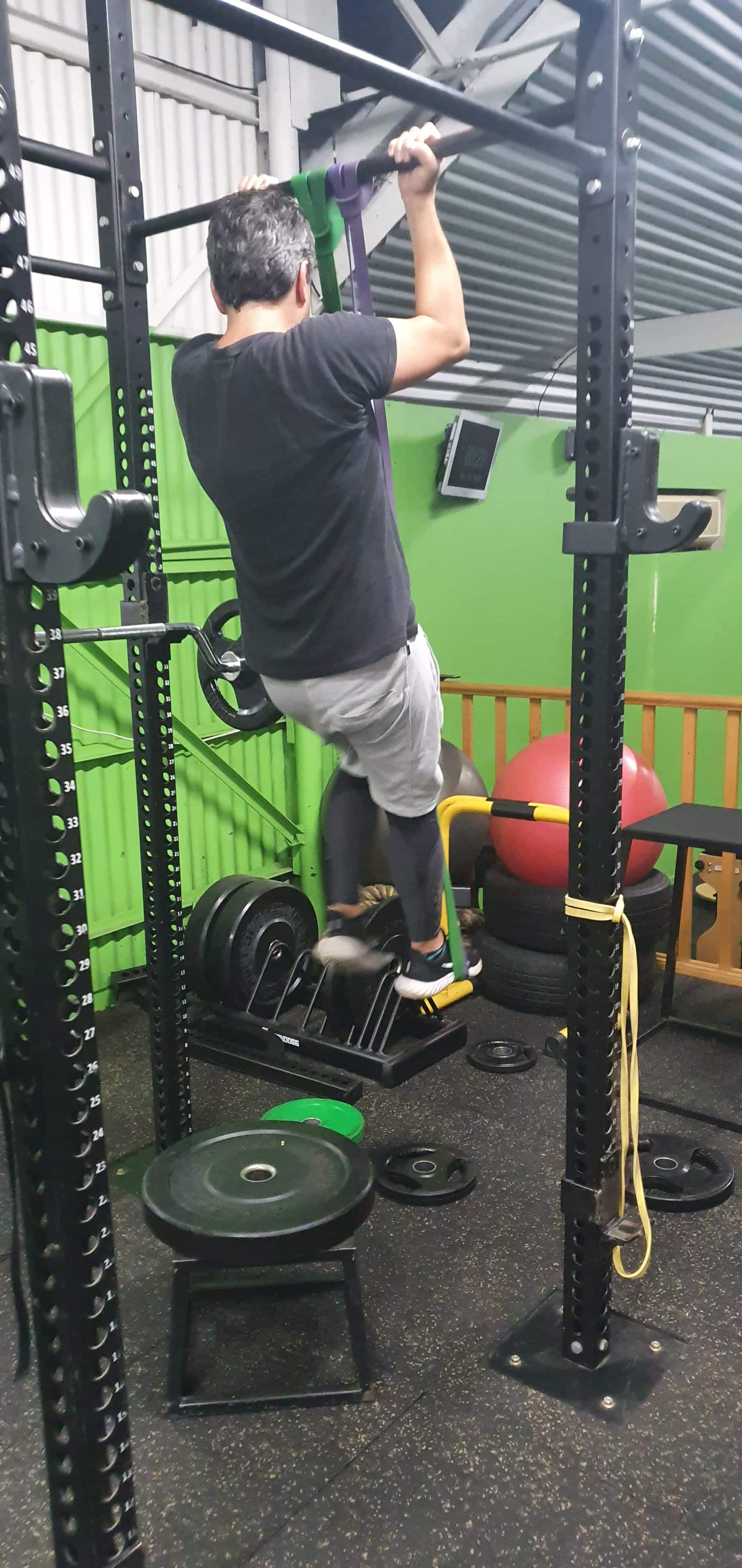 Strength training man performing a chin up in the gym