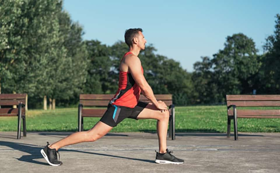 man in lunge position starting to stretch in a park outdoors
